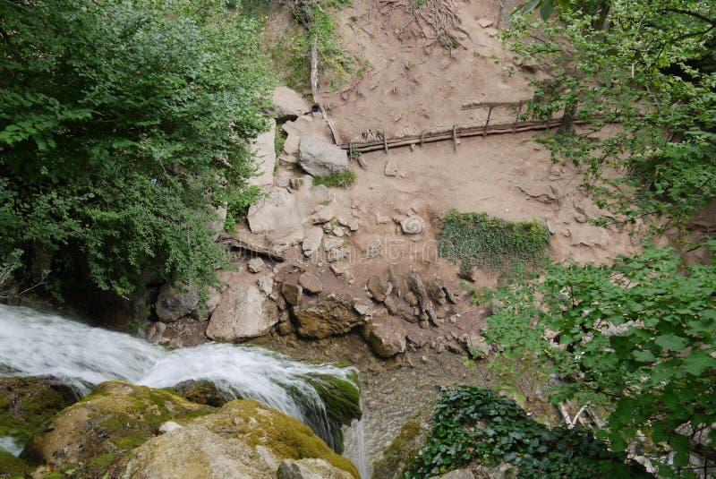 Eine top-down Ansicht eines Wasserfalls, der über Felsen fließt Formung unter einem kleinen Teich und Betrieb weiter in die Tiefe lizenzfreie stockfotos