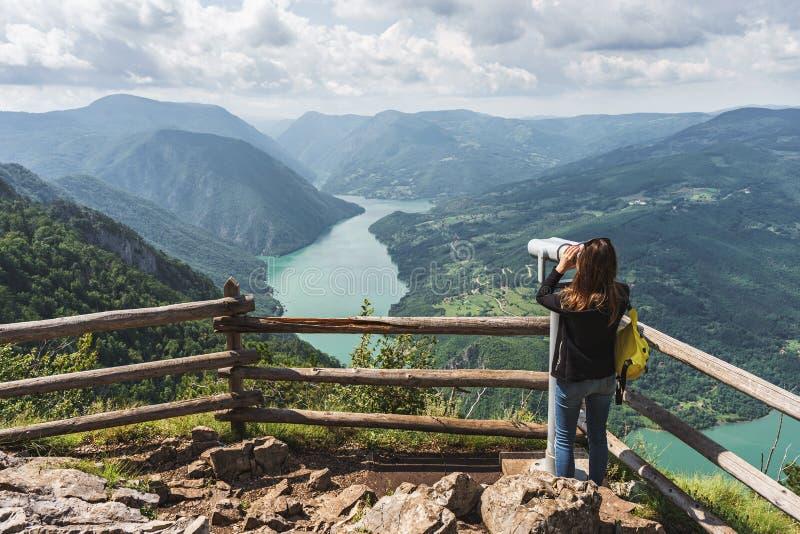 Eine touristische Frau betrachtet die schöne Natur durch ein stationar lizenzfreie stockbilder