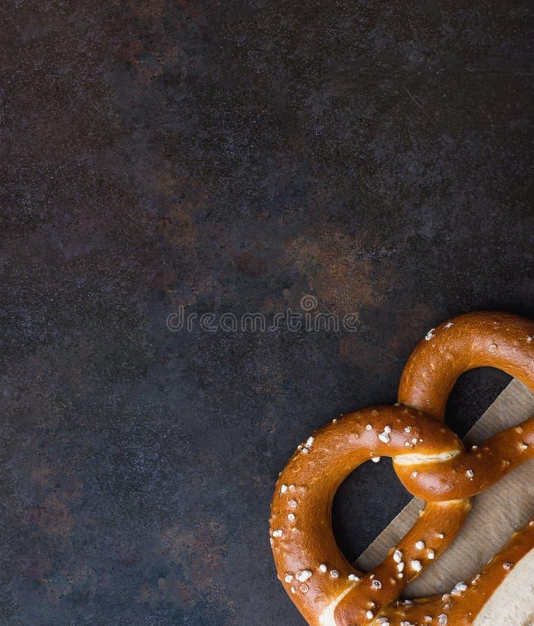 Eine traditionelle deutsche wohlschmeckende Laugen-Brezel mit Salz auf Stück Pergamentpapier auf dunklem rustikalem Rusty Backgro stockfotos