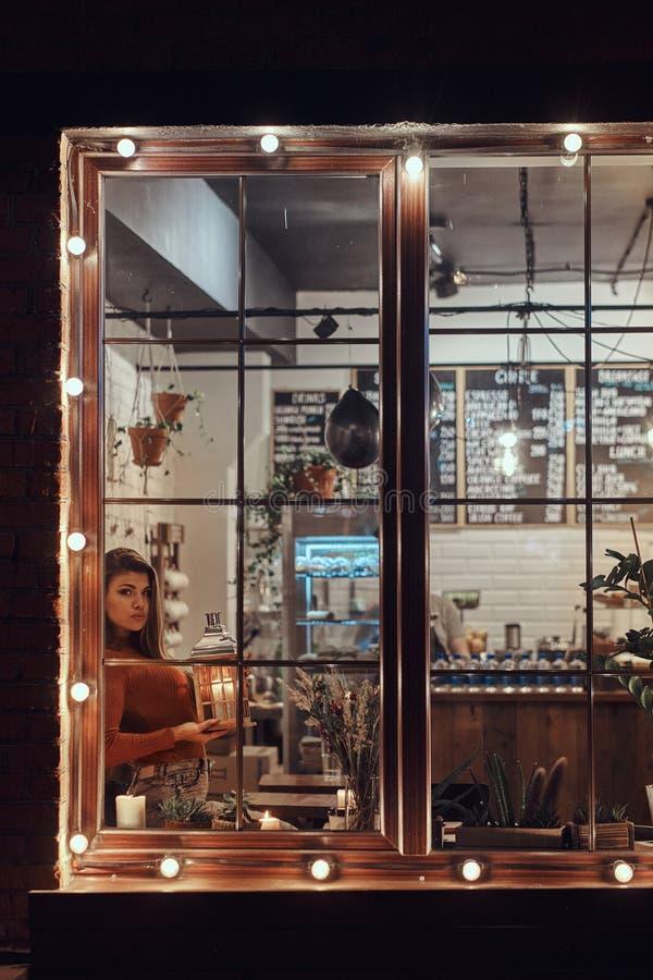 Eine tragende Strickjacke des schönen Mädchens, die eine Kerzenlaterne beim Sitzen auf einem Fensterbrett innerhalb des Cafés häl lizenzfreie stockfotografie
