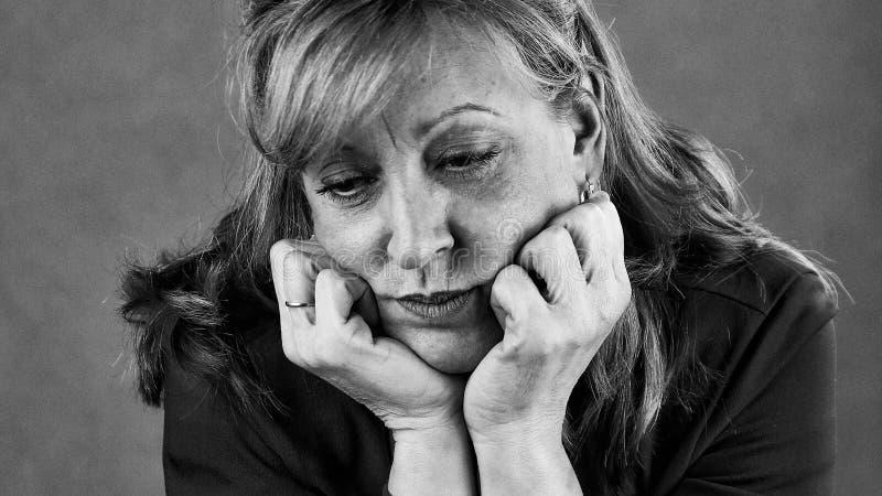 Eine traurige deprimierte Frau in Schwarzweiss stockfotografie