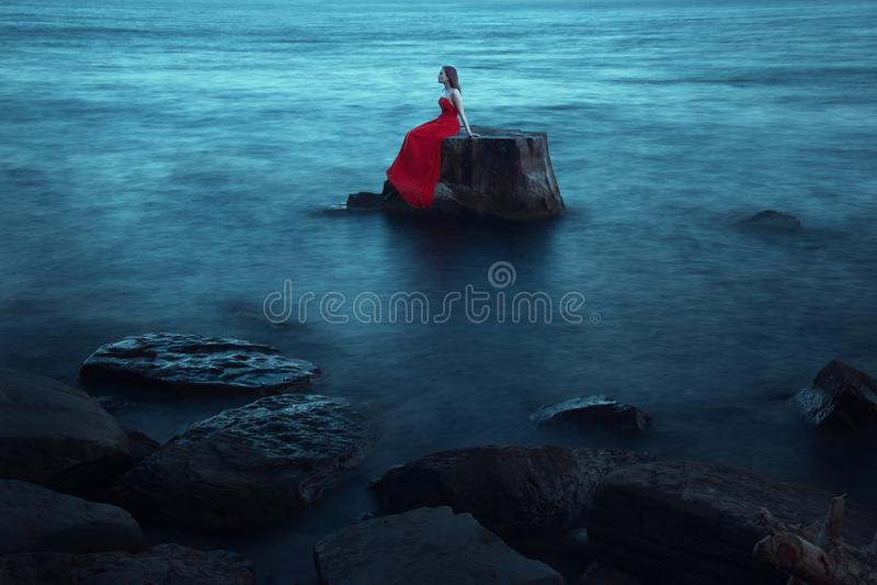 Eine traurige Frau nahe dem Meer am Abend lizenzfreies stockbild