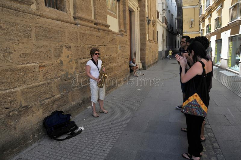 Eine Unbekanntfrau spielt das Saxophon auf der alten Straße der Stadt von Cadiz stockbilder