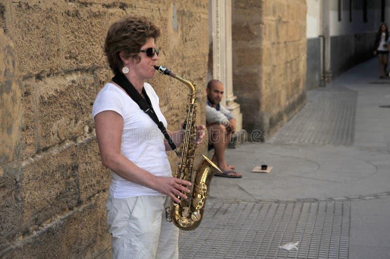 Eine Unbekanntfrau spielt das Saxophon auf der alten Straße der Stadt von Cadiz lizenzfreie stockfotos