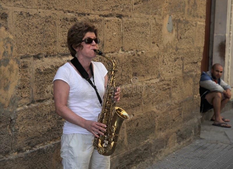 Eine Unbekanntfrau spielt das Saxophon auf der alten Straße der Stadt von Cadiz stockfoto