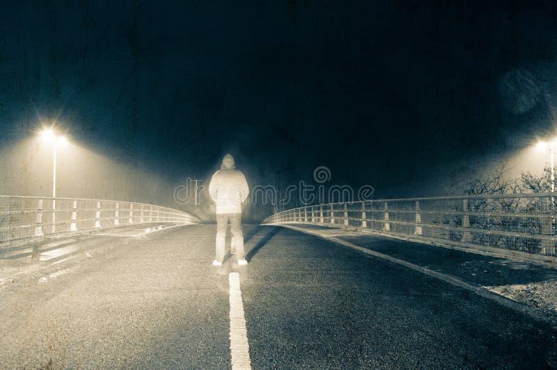 Eine unscharfe mit Kapuze Zahl Stellung mitten in der Straße auf einer Winternacht, wenn die Autoscheinwerfer oben hinter ihm erl lizenzfreies stockbild