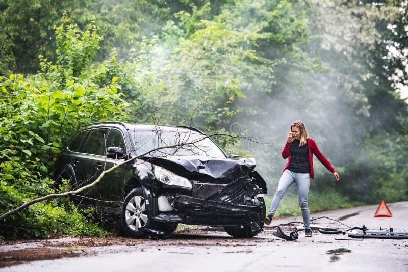 Eine verärgerte junge Frau mit Smartphone durch das beschädigte Fahrzeug nach einem Autounfall stockfotografie