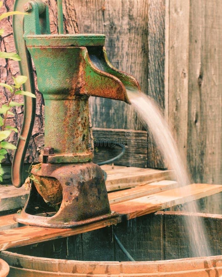 Eine verrostete grüne QuellwasserHandpumpe lizenzfreie stockfotografie