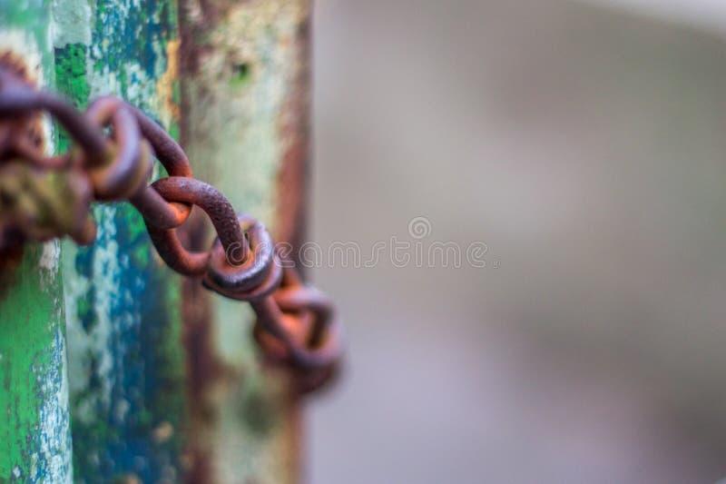 Eine verrostete Kette gegen verrostetes Tor lizenzfreie stockfotografie