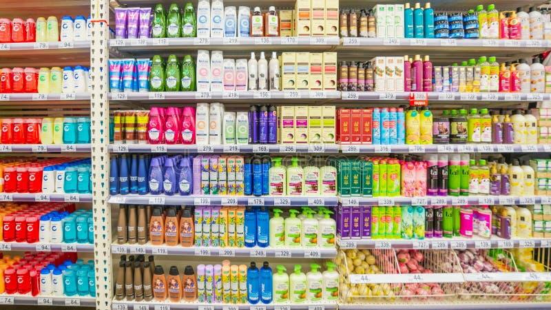 Eine verschiedene Auswahl des Shampoos und anderer Reinigungsmittel auf den Supermarktregalen Text auf russisch: Shampoo, Massage stockfoto