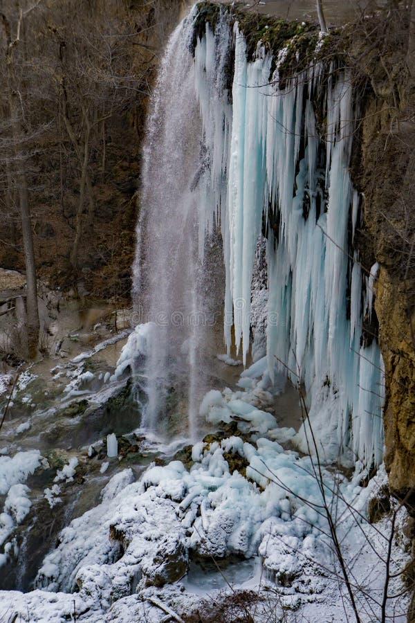 Eine vertikale Ansicht des gefrorenen fallenden Frühlinges fällt stockfotografie