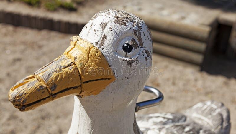 Eine verwitterte hölzerne Ente auf Spielplatznahaufnahme stockbilder
