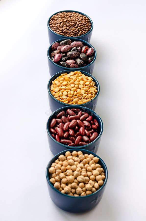Eine Vielzahl von H?lsenfr?chte Linsen, Kichererbsen, Erbsen und Bohnen in den blauen Sch?sseln auf einem wei?en Hintergrund Naha lizenzfreie stockfotos