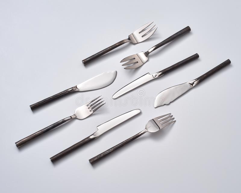 Eine Vielzahl von Löffeln, von Messern und von Gabeln auf einem grauen Hintergrund mit Raum für Text vektorabbildung getrennt auf lizenzfreie stockfotografie