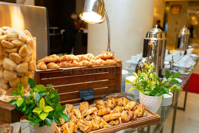 Eine Vielzahl von Plätzchen auf hölzernen Behältern, von Keksplätzchen in einem Klarglasvase, von Hörnchen, von Samowaren mit Tee stockfotografie