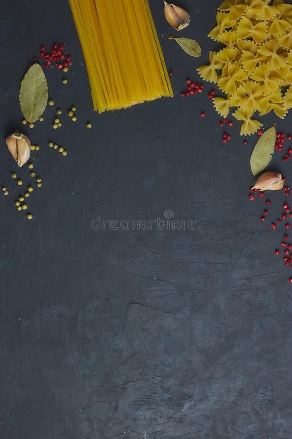 Eine Vielzahl von rohen Teigwaren nahe bei den Gewürzen und den Gewürzen auf schwarzem konkretem Hintergrund Ansicht von oben Kop stockfoto
