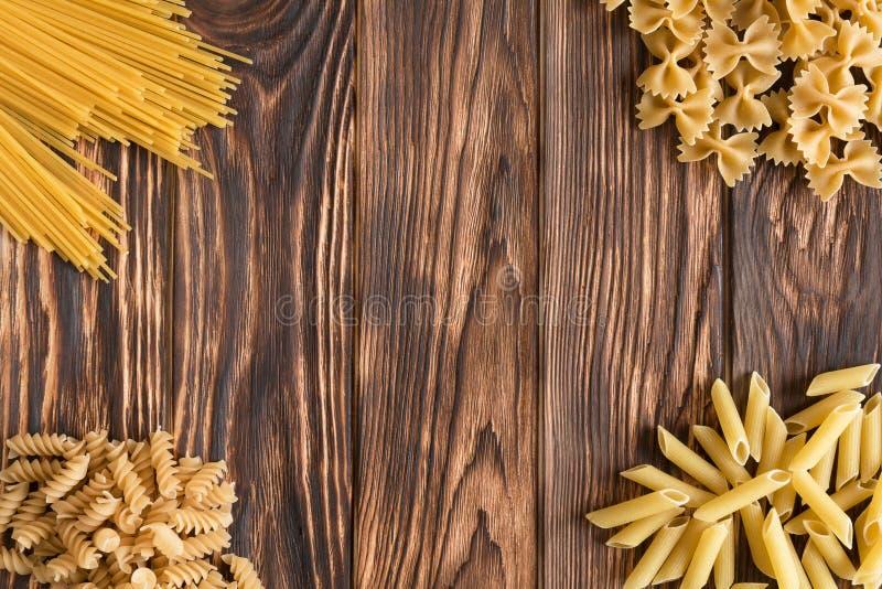 Eine Vielzahl von Vielzahl von Teigwaren auf einem schönen Holztisch lizenzfreie stockfotografie