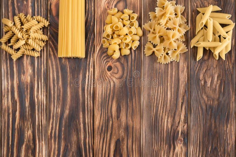 Eine Vielzahl von Vielzahl von Teigwaren auf einem schönen Holztisch lizenzfreies stockbild