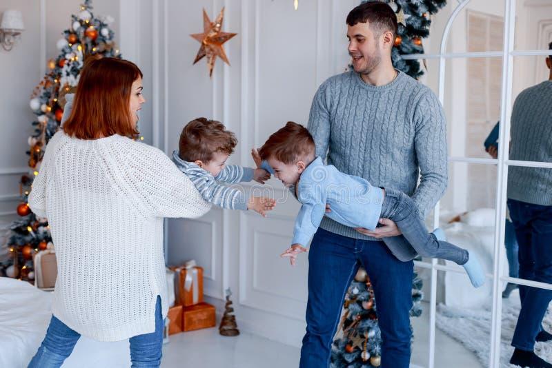 Eine vierköpfige Familie, die vor dem Weihnachtsbaum umarmt Liebe, Glück und großes Familienkonzept lizenzfreie stockfotos