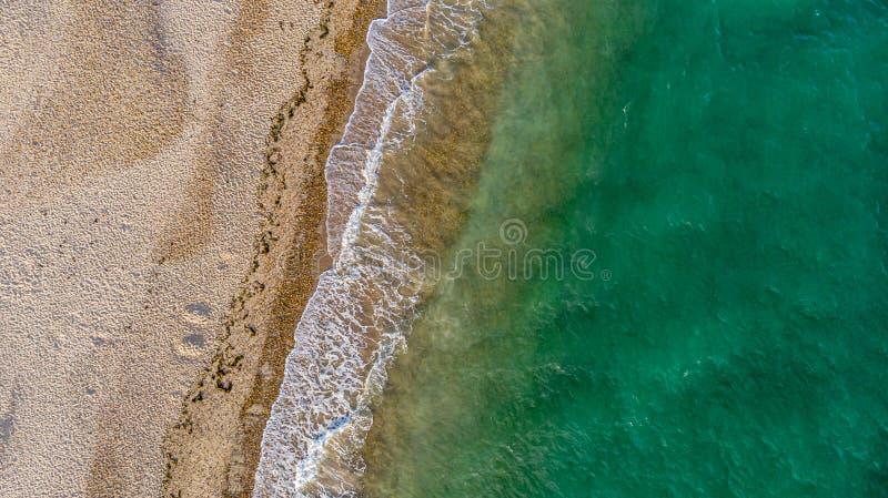 Eine Vogelperspektive eines sonnigen sandigen Strandes mit zusammenstoßenden Wellen und grünem Kristallwasser stockbilder