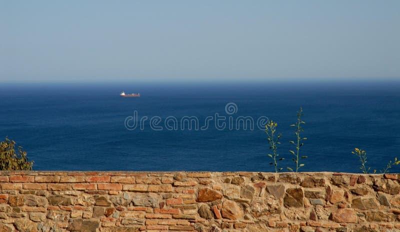 Eine Wand, das Meer, der Himmel und ein Schiff nahe Màlaga in Spanien stockfoto