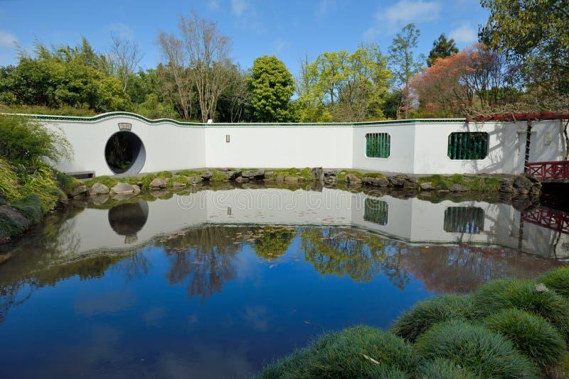 Eine Wand reflektierte sich im ruhigen Wasser von einem Teich stockbild