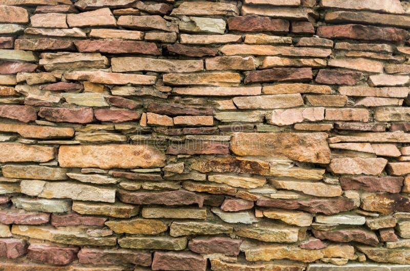 Eine Wand von kleinen Steinen Beschaffenheit von gelben Steinen Steiniger Hintergrund lizenzfreies stockfoto
