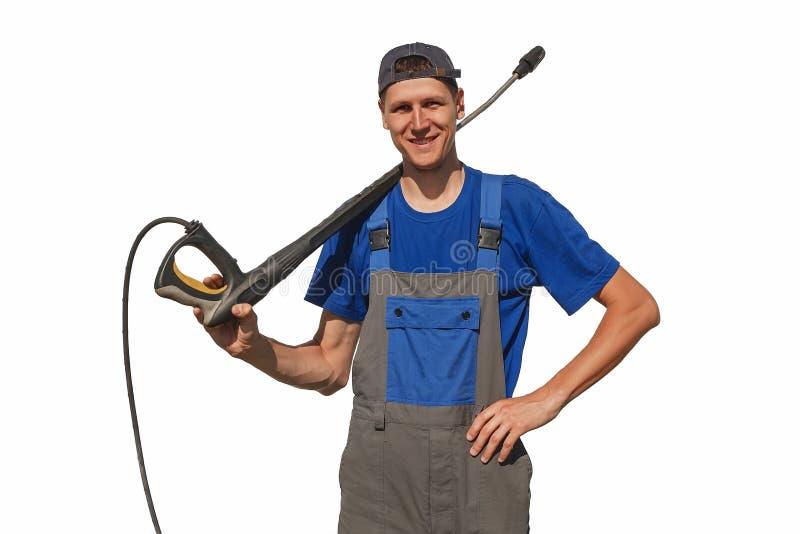 Eine Waschanlagearbeitskraft mit der Ausrüstung lokalisiert auf einem weißen Hintergrund Der nette Kerl in den Overallblicken in  stockfoto