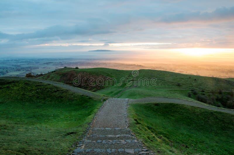 Eine Wegüberschrift in das abschüssige Auf dem Eisenzeitalter-Hügelfort des britischen Lagers, Malvern-Hügel Wenn die Sonne auf e stockbilder