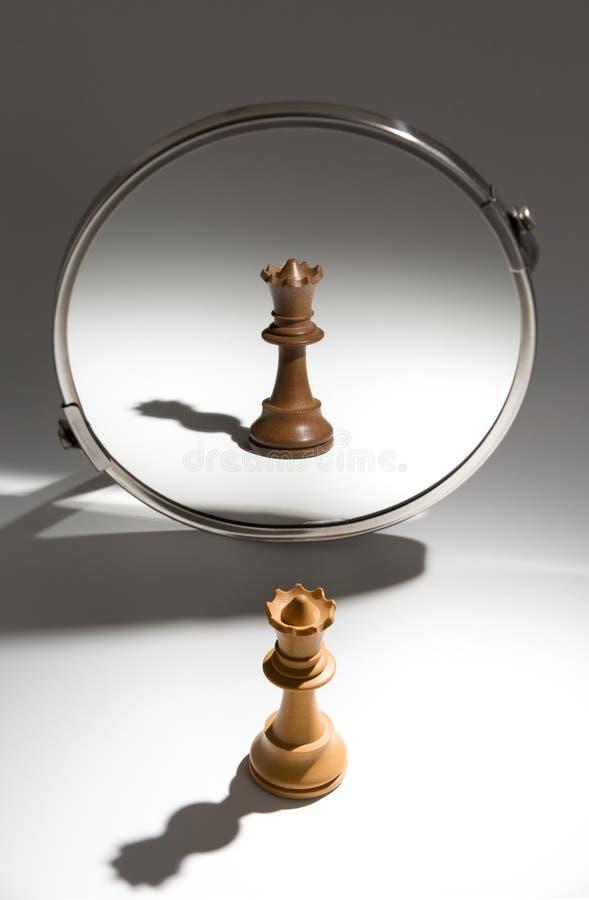Eine weiße Königin schaut in einem Spiegel, um sich als schwarze Königin zu sehen stockbild