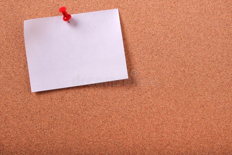 Eine weiße klebrige Beitragsanmerkung steckte KorkenAnschlagbrett-Kopienraum fest stockbild