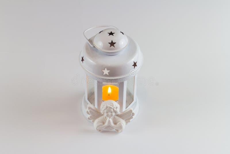 Eine weiße Laternenkerze mit einem Gipsengel lizenzfreies stockbild