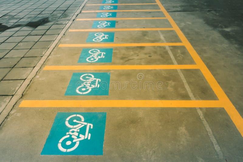 Eine weiße Malerei eines Fahrrades auf dem Asphalt der Straße, die Kennzeichen des Fahrradparkens bedeutet stockfotografie