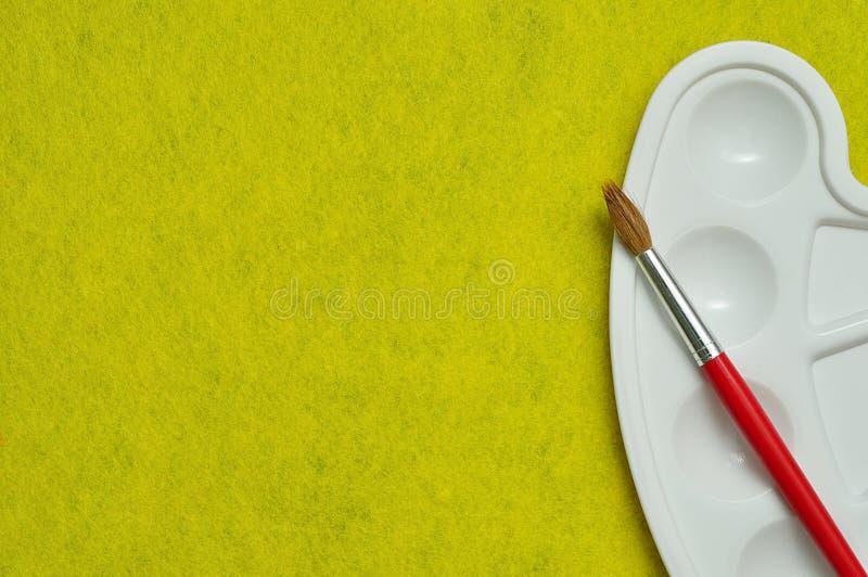 Eine weiße Palette mit einem Pinsel lizenzfreie stockbilder