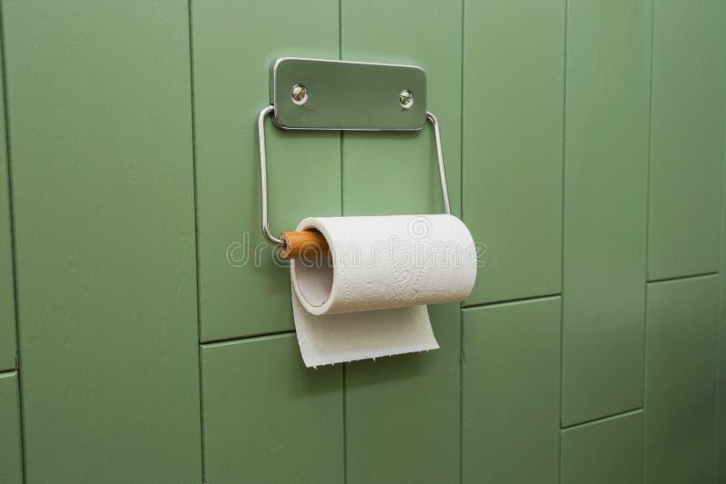 Eine weiße Rolle des weichen Toilettenpapiers, das ordentlich an einem modernen Chromhalter auf einer grünen Badezimmerwand hängt lizenzfreie stockfotografie