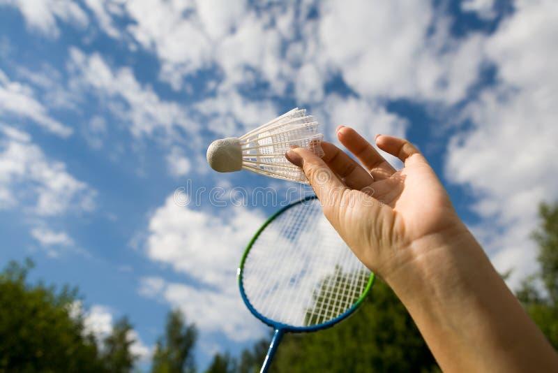 Eine weibliche Hand hält einen Federball gegen den Himmel lizenzfreies stockfoto