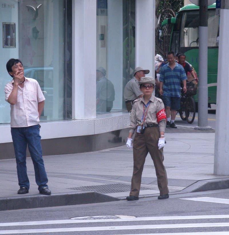 Eine weibliche Polizei leitet den Verkehr stockbilder