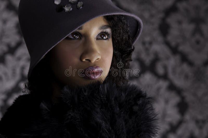Herrliche dunkelhäutige Frau in der Dreißigerjahre Weinlesekleidung stockfoto