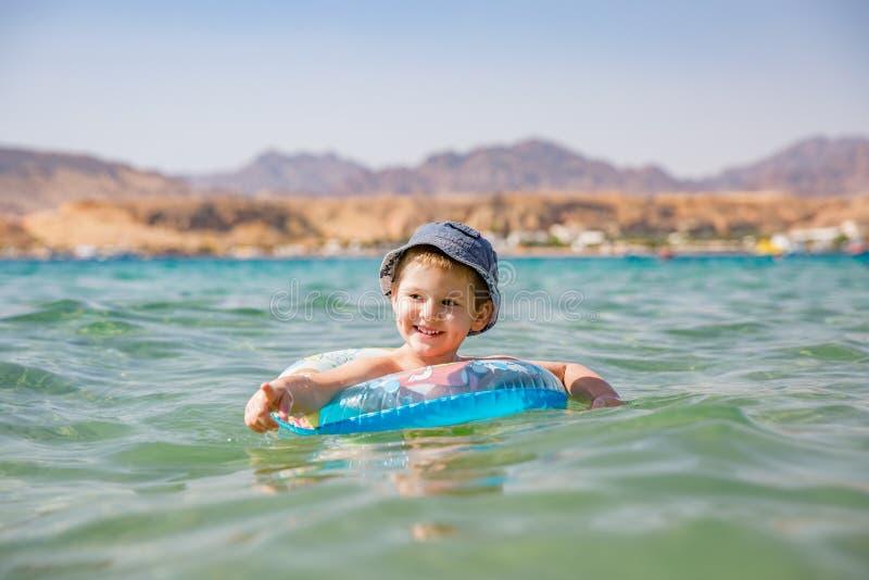 Eine wenig nette Jungenschwimmen im Meer Glückliches Jungenspielen, schwimmend im Meer mit aufblasbarem Ring lizenzfreie stockfotos