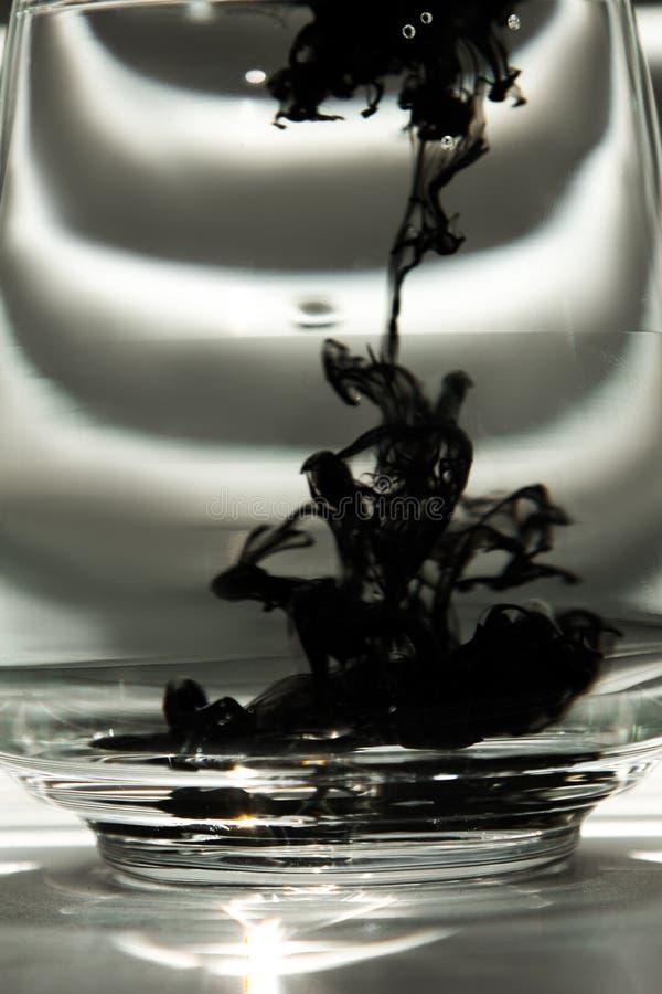 Eine Wolke der Tinte in einer transparenten Glasschale mit klarem Wasser gegen den Hintergrund eines gestreiften Schirmes mit Str lizenzfreies stockbild
