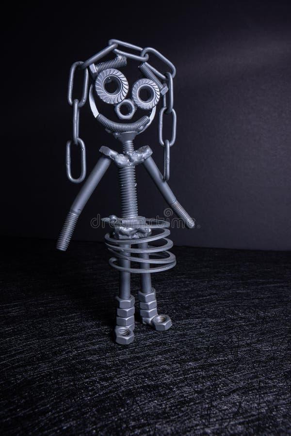 Eine Zahl von einem kleinen Roboter zusammengebaut von einigen Bolzen und von N?ssen, die in einer vertikalen Position stehen Es  stockfoto