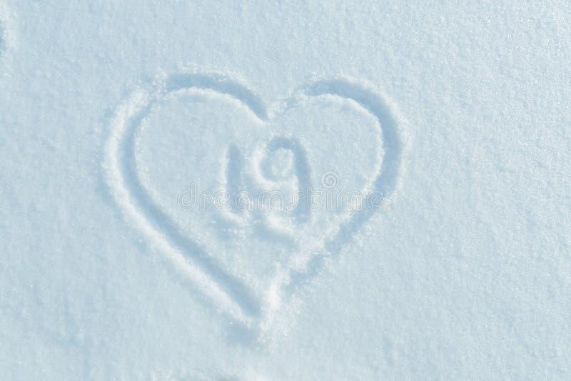 Eine Zahl von neunzehn geschrieben in den Schnee im gemalten Herzen stockfotos