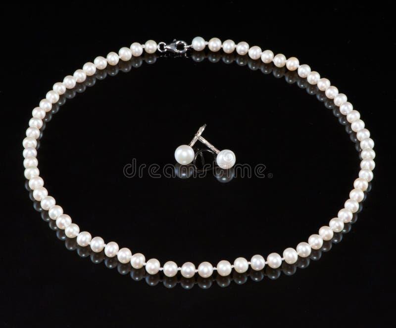 Eine Zeichenkette der Perlen und der Ohrringe stockfotos