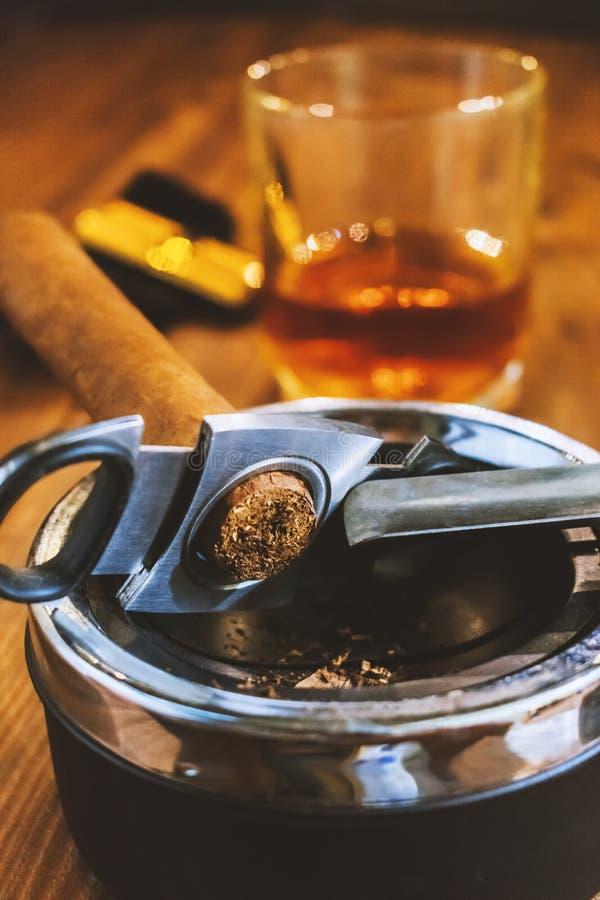 Eine Zigarre mit einer Guillotine im Aschenbecher im Vordergrund stockfotos