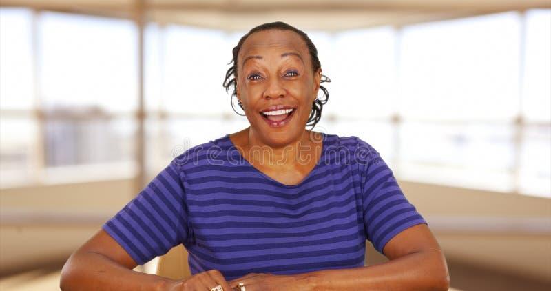 Eine zufällig gekleidete schwarze Geschäftsfrau, die an der Kamera lächelt lizenzfreie stockbilder
