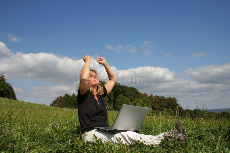 Eine zujubelnde Frau mit einem Laptop stockfoto