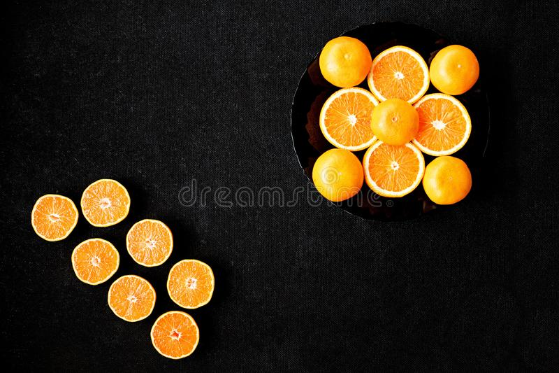 Eine Zusammensetzung des Schnittes in den Hälfteorangen und -tangerinen auf einem schwarzen Hintergrund lizenzfreie stockfotos