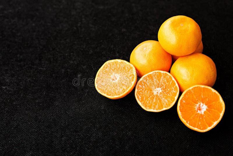 Eine Zusammensetzung des Schnittes in den Hälfteorangen und -tangerinen auf einem schwarzen Hintergrund lizenzfreies stockbild