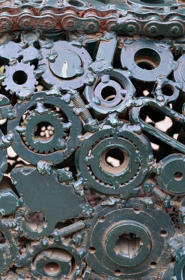 Eine Zusammensetzung eines Satzes Gänge und Autoteile, die miteinander und gemaltes Grün geschweißt werden Schmutz steampunk text lizenzfreie stockfotografie