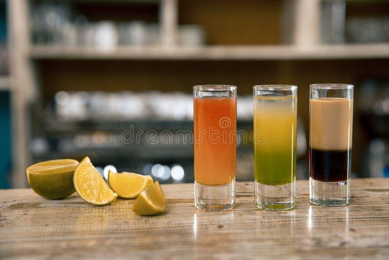 Eine Zusammensetzung von drei bunten Schussgetränken Alkoholische Cocktails mit Kalk auf einem Barhintergrund lizenzfreies stockfoto